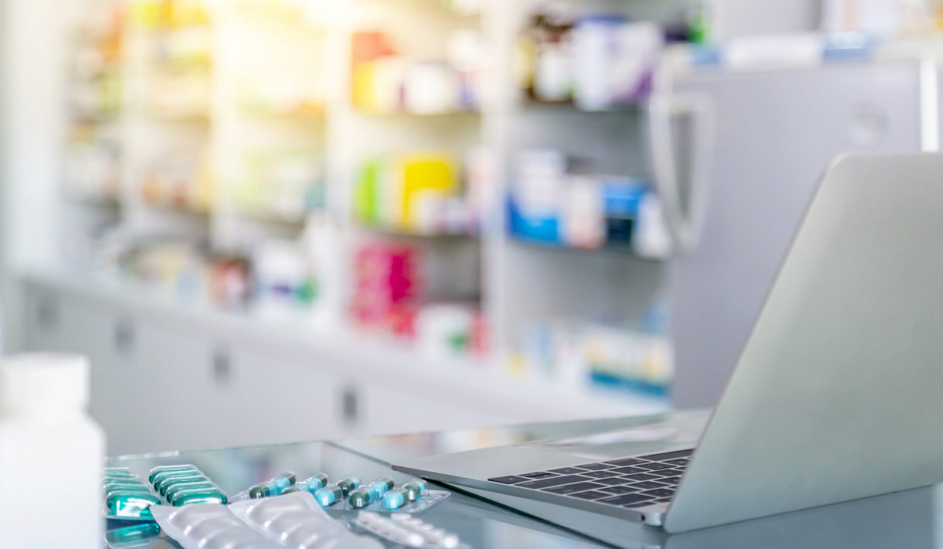 Medicine And Computer On Payment Counter With Blurred Medicines Shelves Background. Healthcare, Medical And Pharmacy Concept.